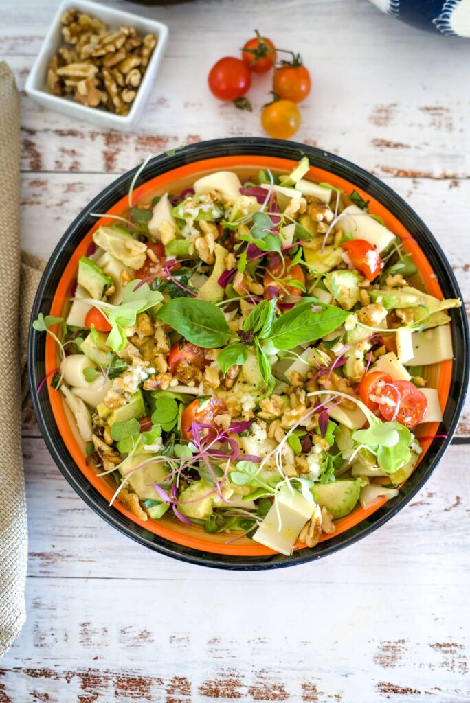 palm hearts, avocado, tomato and walnut salad in a serving bowl.